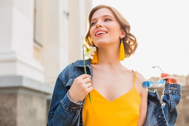 Bella donna sensuale che guarda avanti, indossa una giacca di jeans alla moda e un vestito giallo, tendenza della moda estiva, bellezza naturale, accessori, sorridendo felice