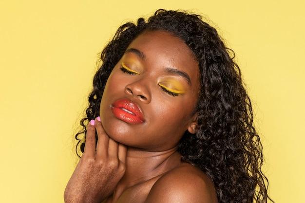 桃のリップグロスを身に着けている官能的な黒人女性