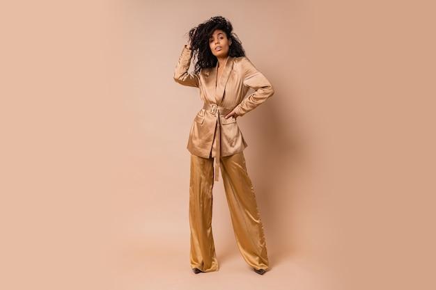 베이지 색 벽 위에 포즈 우아한 황금 새틴 정장에 아름다운 물결 모양의 머리카락과 관능적 인 흑인 여성. 봄 패션 봐. 전체 길이.