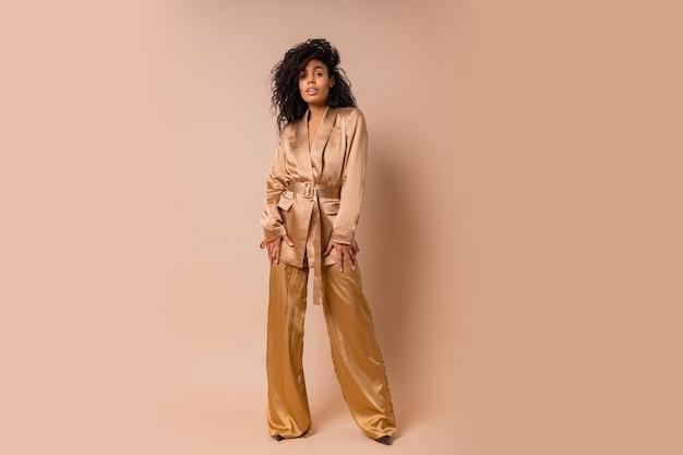 Чувственная темнокожая женщина с красивыми волнистыми волосами в элегантном золотом атласном костюме позирует над бежевой стеной. весенний модный образ. полная длина.