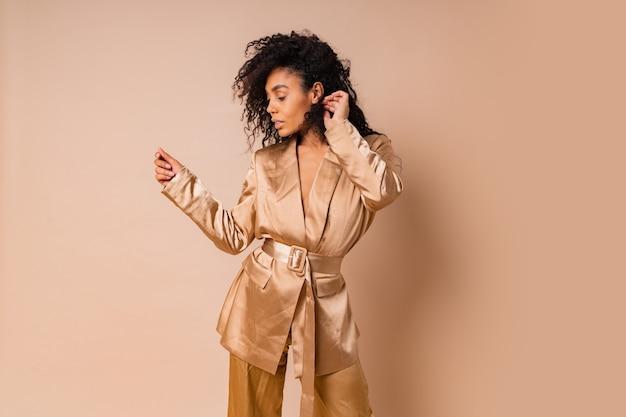 베이지 색 벽 위에 포즈 우아한 황금 새틴 정장에 아름다운 물결 모양의 머리카락과 관능적 인 흑인 여성. 봄 패션 봐.