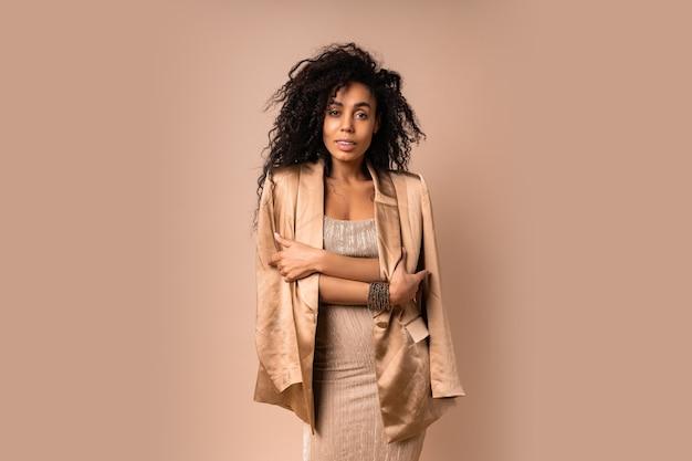 황금 반짝 고급스러운 드레스 포즈에 아름다운 물결 모양의 머리카락과 관능적 인 흑인 여성.