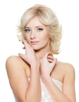 白い壁でポーズ新鮮な健康肌と官能的な金髪の女性
