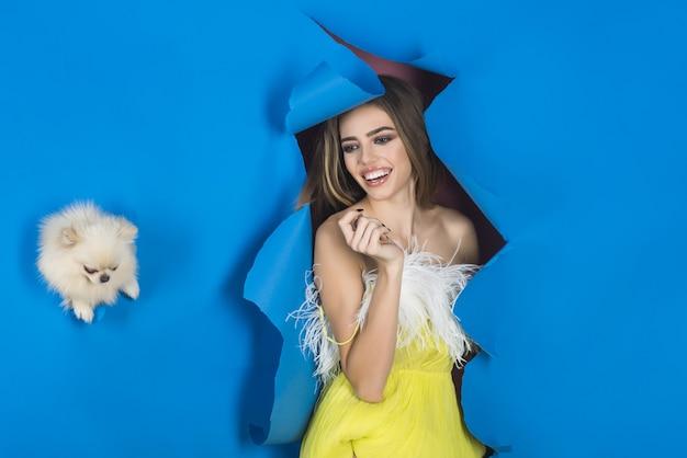 Чувственная светловолосая модель в желтом платье и милый маленький щенок в дырке в синей бумаге проходит через нее