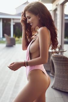 Sensual brunette model in fashion swimsuit posing on terrace