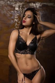 스튜디오에서 포즈를 취하는 섹시한 란제리에 운동 몸을 가진 관능적 인 갈색 머리 모델