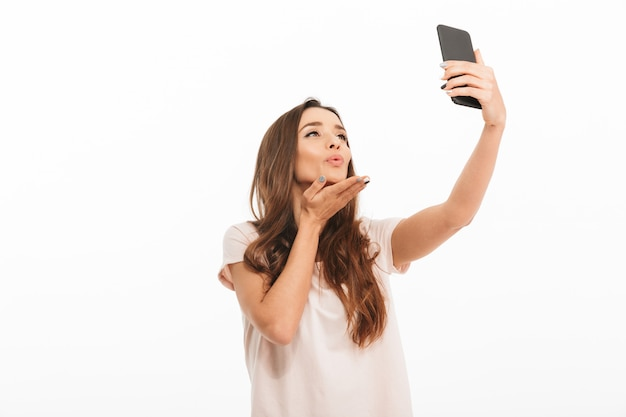 Sensual brunette woman in t-shirt making selfie on smartphone and sends air kiss over white wall