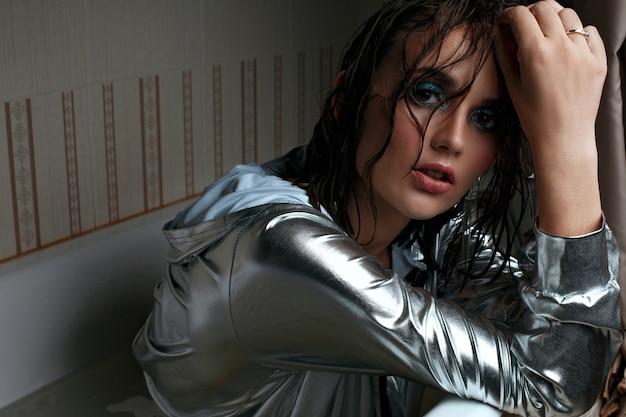 목욕에서 포즈를 취하는 은색 재킷을 입고 아름다운 화장을 한 관능적 인 갈색 머리 여자. 텍스트를 위한 공간