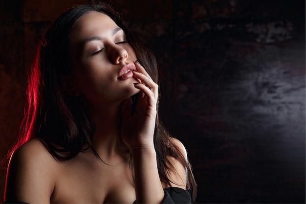 スタジオで赤い光と影でポーズをとって目を閉じて官能的なブルネットの女性