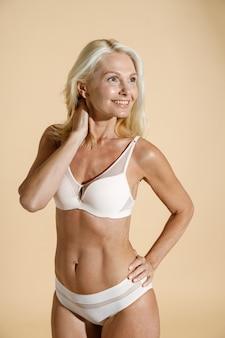 官能的な白人の成熟したブロンドの女性のランジェリーは、半分裸で孤立したポーズをとって笑っている