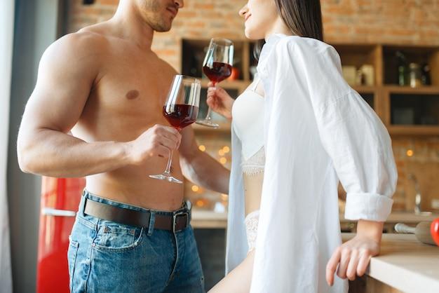 官能的なカップルがキッチンでロマンチックなディナーを過ごす