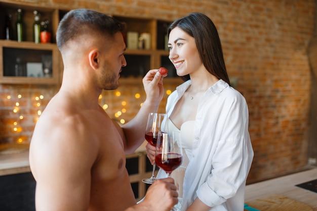 관능적 인 커플은 함께 부엌에서 낭만적 인 저녁 식사를 보냅니다. 집에서 아침 식사를 준비하는 남자와 여자, 에로티시즘 요소가있는 음식 준비