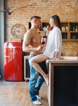 관능적 인 커플은 함께 부엌에서 낭만적 인 친밀한 저녁 식사를 보냅니다. 집에서 아침 식사를 준비하는 남자와 여자, 에로티시즘 요소가있는 음식 준비
