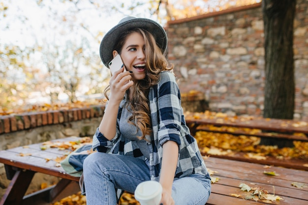 Sensual curly woman in hat expressing funny emotions during photoshoot in autumn yard