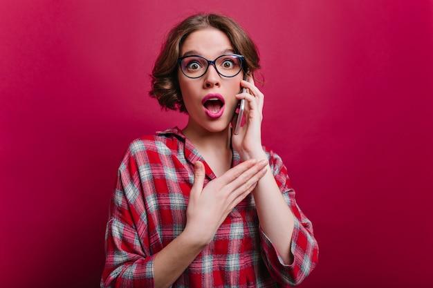 驚いた表情で電話で話している流行のシャツを着た官能的な暗い目の女の子。スマートフォンを持って驚きを表現する魅力的な若い女性の屋内の肖像画。