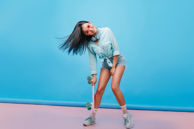 Sensual dark-haired girl in casual street outfit dancing, holding longboard. catching hispanic woman in sneakers  posing with smile.