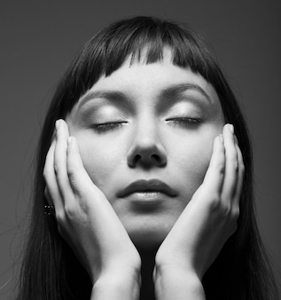 Sensual dark portrait of a young woman with closed eyes