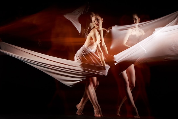 The sensual and emotional dance of beautiful ballerina with white fabric