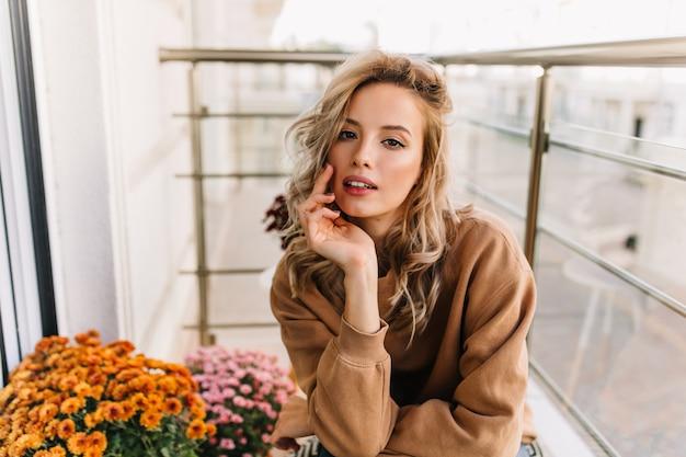 テラスに座っている官能的なヨーロッパの女の子。花の横でポーズをとる興味のあるきれいな女性の肖像画。
