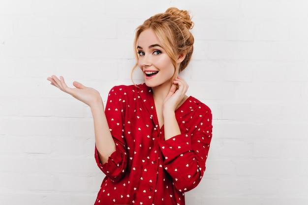 Чувственная светловолосая девушка с милой прической позирует в пижаме. крытый портрет веселой молодой женщины в красных пижамах улыбается