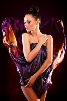 밝은 다채로운 비행 드레스 포즈 아름 다운 섹시 한 갈색 머리 소녀 모델의 관능적 인 패션 초상화, birght 메이크업 검은 배경에 고립