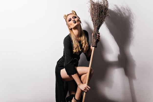 빗자루와 함께 포즈 마녀 의상에서 관능적 인 여성 모델. 얼굴 표정 키스와 흰 벽에 서있는 우아한 뱀파이어 소녀.