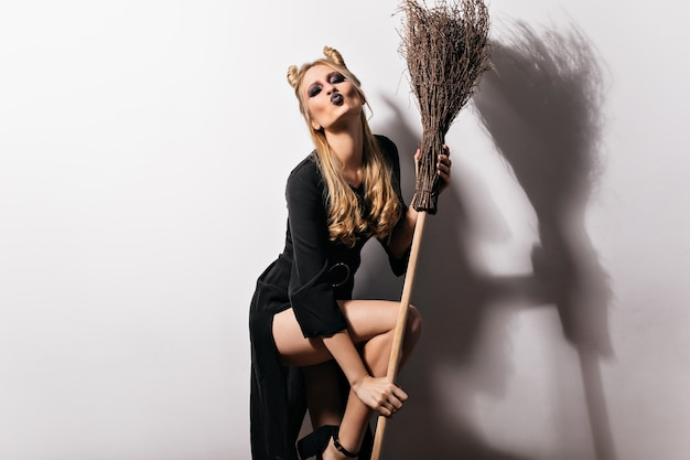 Sensual female model in witch costume posing with broom. graceful vampire girl standing on white wall with kissing face expression.