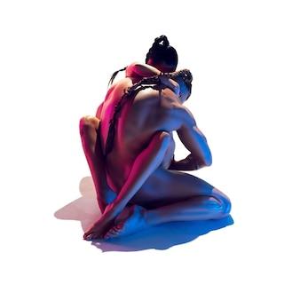 Coppia in forma sensuale isolata sulla parete bianca dello studio in luce al neon