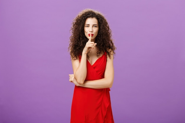 Sensual and flirty elegant european woman with curly hairstyle and lipstick in red evening dress smirking saying shh showing shush gesture with index finger over mouth having secret over purple wall.