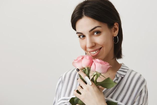 웃 고 장미 꽃다발을 들고 관능적 인 꼬리 치는 여자