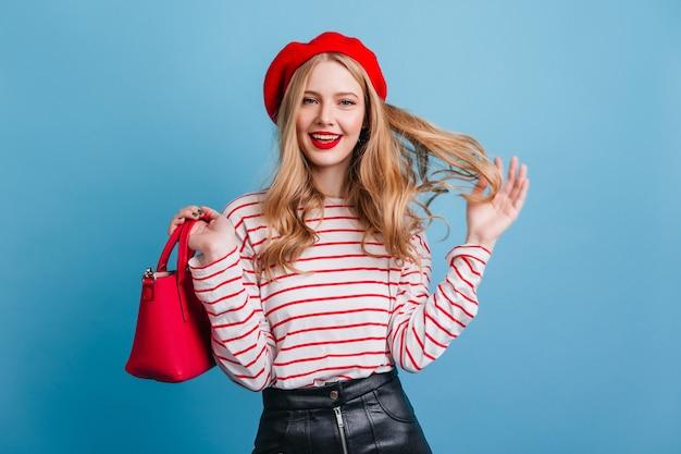 ブロンドの髪で遊ぶ官能的なフランスの女の子。青い壁に分離されたベレー帽の笑顔の若い女性。