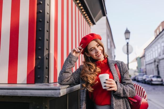 Sensuale ragazza francese con il manicure nero che gode del servizio fotografico sul viale nella mattina di autunno
