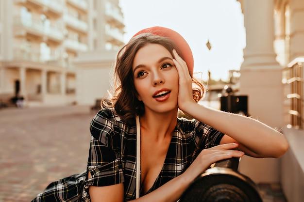 벤치에 앉아 우아한 헤어 스타일으로 관능적 인 프랑스 소녀. 도시에 포즈를 취하는 빨간 베레모에 아름 다운 유럽 여자의 야외 초상화.