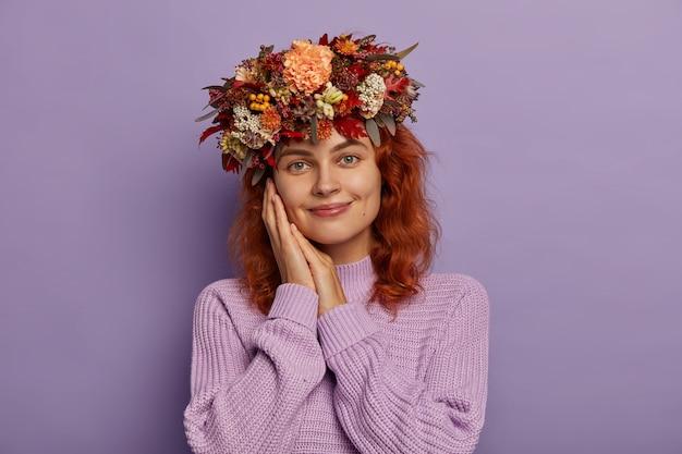 관능적 인 생강 유럽 여성은 양손을 뺨 근처에 유지하고, 뺨에 보조개로 미소를 짓고, 멋진 가을 화환을 착용하고, 니트 오버 사이즈 점퍼를 입고