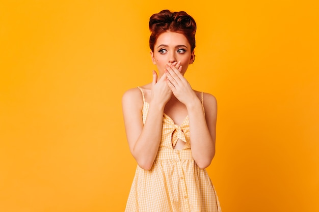 Sensual ginger woman covering mouth with hands. studio shot of trendy pinup female model isolated on yellow space.
