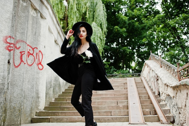 Sensual girl all in black, red lips and hat. goth dramatic woman hold white chrysanthemum flower against graffiti wall.