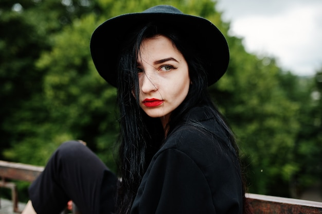 Sensual girl all in black, red lips and hat. goth dramatic woman.