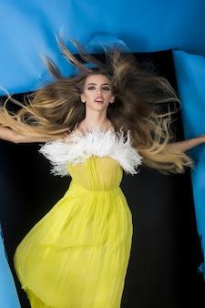 Чувственная девушка проходит через дырку в голубой бумаге. уверенная блондинка в желтом платье проходит сквозь дырку в бумаге. модная одежда. модные товары. летняя распродажа. продажи.