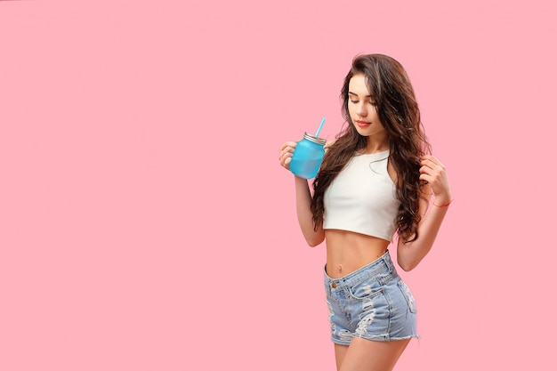 Sensual girl in summer outfit with drink