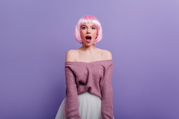 Sensual girl with short pink hair looking with amazement. indoor photo of magnificent young lady in white skirt isolated on purple wall.