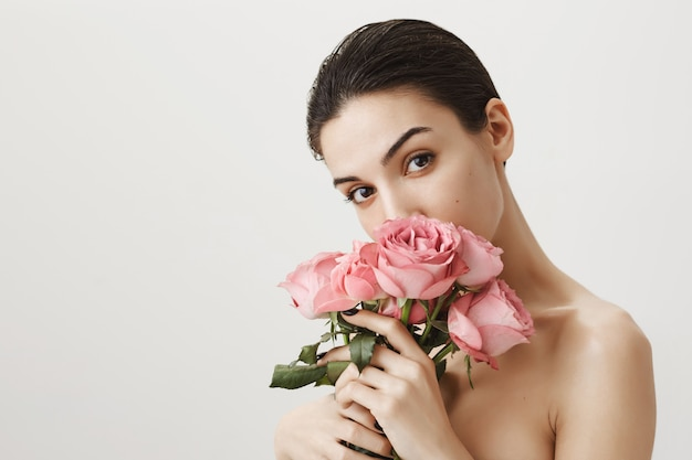Sensual girlfriend smelling bouquet of roses while standing naked on grey