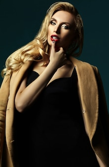 Sensual glamour portrait of beautiful blond woman model lady with fresh makeup in classic black costume and overcoat touching lips