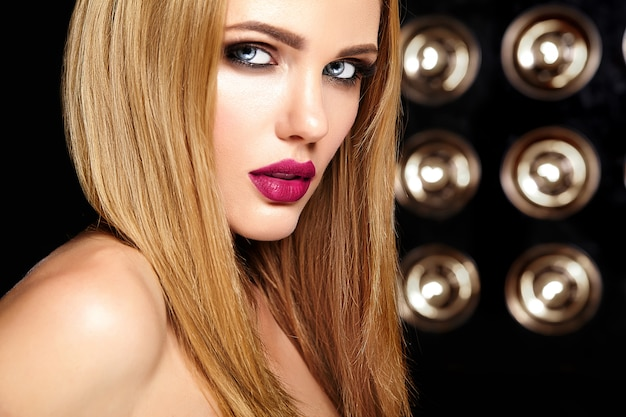 Sensual glamour portrait of beautiful woman model with fresh daily makeup with pink lips color and clean healthy skin face on studio lights background