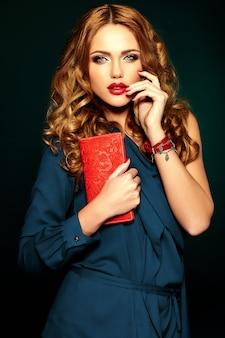 赤い唇の色ときれいな健康な肌と新鮮な毎日のメイクで美しい女性モデルの官能的な魅力の肖像画。財布を手に