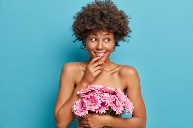 Sensual happy female model with healthy naked body, holds bouquet of pink gerberas flowers, looks with dreamy cheerful expression aside, stands