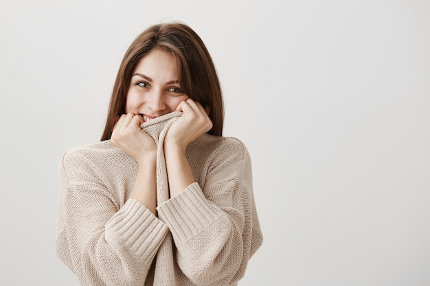 Sensual happy woman giggle and hiding smile behind sweater