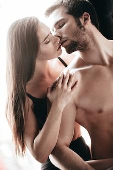 官能的なキス。窓枠に座ってハンサムな彼氏にキスする下着姿の美しい若い女性