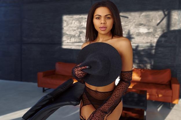 섹시 한 란제리의 관능적 인 여자는 검은 모자를 보유