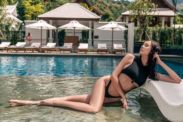 Sensual lady resting near the pool