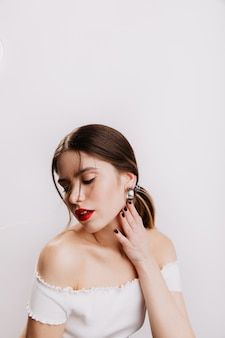 Sensual lady with plump red lips gently touches her neck, looking down. shot of brown-haired girl in white top.